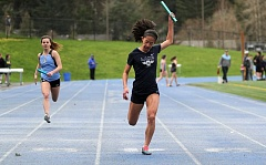 REVIEW PHOTO: MILES VANCE - Lake Oswego's Erica Chiang finishes off her team's win in the 4 x 100-meter relay during the Lakers' 88-56 win over Lakeridge on Wednesday at Lakeridge High School. Lakeridge's Emily Bell is at left.